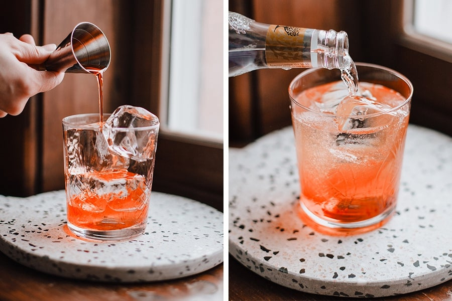 Hand pours a jigger of alcohol in an old-fashioned glass filled with ice.